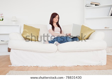 Good looking red-haired woman relaxing with her laptop while sitting on a sofa in the living room