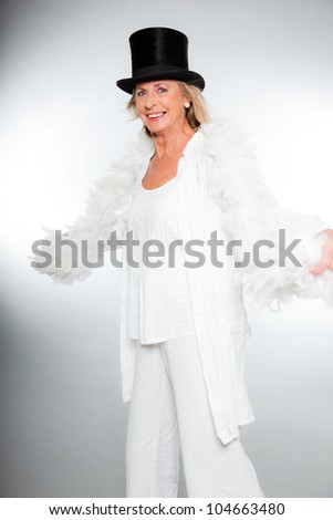 Good looking senior blond woman isolated on white background. Dressed in white and wearing black hat and white boa. Expression and emotion. Studio shot. - stock photo