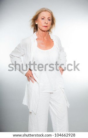 Good looking senior blond woman isolated on white background. Dressed in white. Expression and emotion. Studio shot. - stock photo