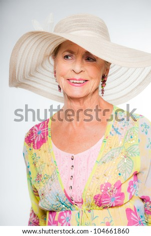 Good looking senior blond woman isolated on white background. Wearing colorful dress with flower pattern and white summer hat. Expression and emotion. Studio shot. - stock photo