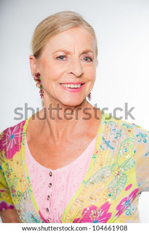 Good looking senior blond woman isolated on white background. Wearing colorful dress with flower pattern. Expression and emotion. Studio shot. - stock photo