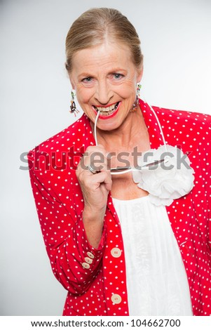 Good looking senior blond woman isolated on white background. Wearing colorful red jacket with white dots and white shirt. Holding white sunglasses. Expression and emotion. Studio shot.