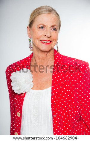 Good looking senior blond woman isolated on white background. Wearing colorful red jacket with white dots and white shirt. Expression and emotion. Studio shot. - stock photo