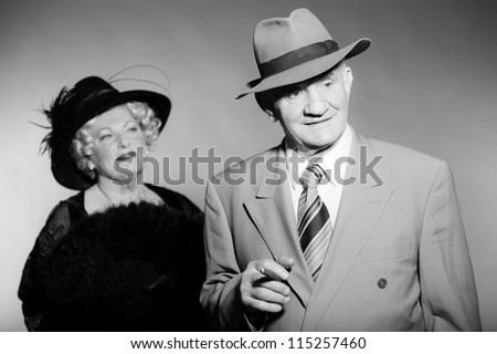 Good looking senior couple glamour vintage style. Wearing a hat. Black and white studio shot. Short blonde curly hair. Chic look. Dressed in black. Wearing a grey suit with tie. - stock photo