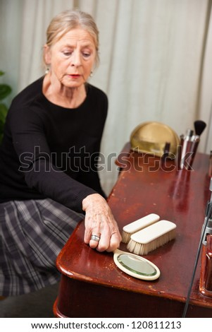 Good looking senior woman sitting behind make-up table.
