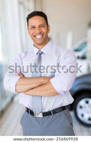 good looking vehicle salesman with arms crossed in car showroom - stock photo