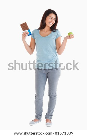 Good looking woman holding a chocolate bar and an apple while standing against a white background