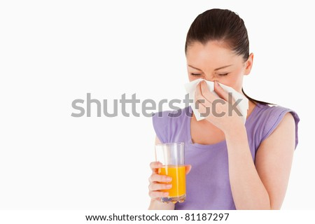 Good looking woman holding a glass of orange juice and sneezing while standing against a white background - stock photo