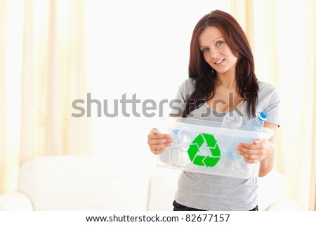 Good looking woman holding recycling bin