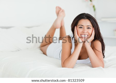 good-looking woman lying on bed with crossed legs looking into camera in bedroom