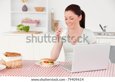 Good looking woman posing with a glass of milk while relaxing with her laptop at lunch time in her kitchen
