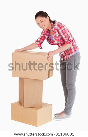 Good looking woman posing with cardboard boxes while standing against a white background