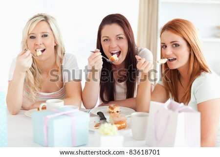 Good-looking Women sitting at a table eating a cake in a kitchen