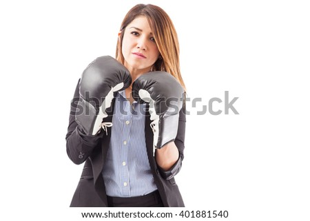 Good looking young brunette wearing a suit and boxing gloves, ready to compete at work