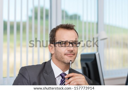 Good looking young businessman wearing glasses sitting thinking at his desk in the office with his pen to his chin as he contemplates a problem - stock photo