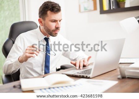 Good looking young businessman with a beard using a laptop computer in his office with reading glasses in his hand