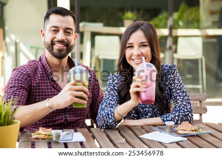 Good looking young couple enjoying some healthy smoothies and sandwiches at a cafe - stock photo