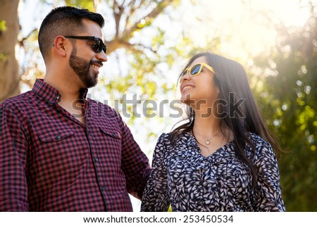 Good looking young couple having fun outdoors and wearing sunglasses - stock photo
