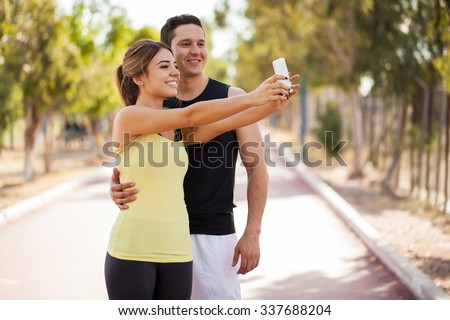 Good looking young couple taking a selfie with a smartphone before working out together in a running track - stock photo