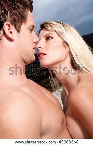 Good looking young couple topless on the beach. - stock photo