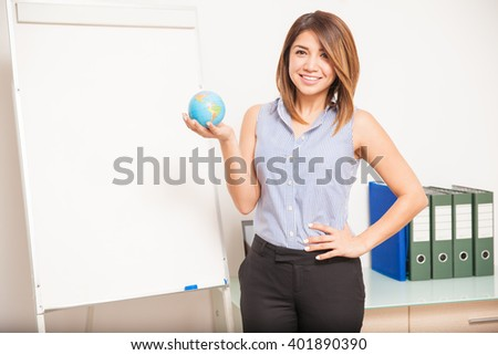 Good looking young female teacher holding a globe and standing next to a flip chart in a classroom - stock photo
