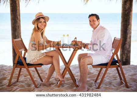 Good looking young Hispanic couple eating lunch and enjoying the ocean view during a romantic date at the beach