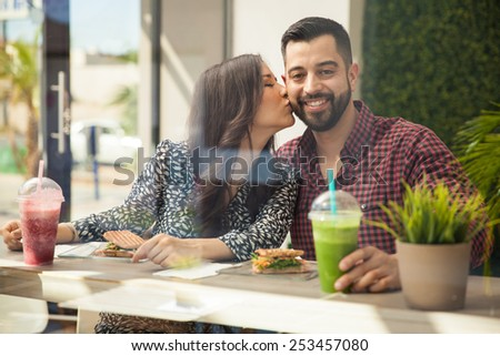 Good looking young man having a healthy lunch with his girlfriend and getting kissed in the cheek - stock photo
