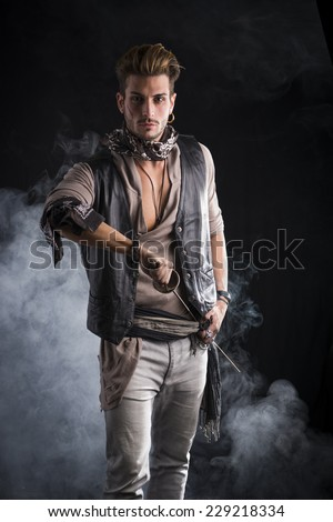 Good Looking Young Man in Pirate Fashion Outfit on Black Background with Smoke. Captured in Studio. - stock photo