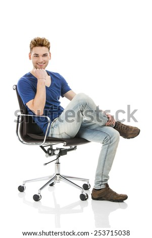 Good looking young man sitting on a chair, isolated on white background - stock photo