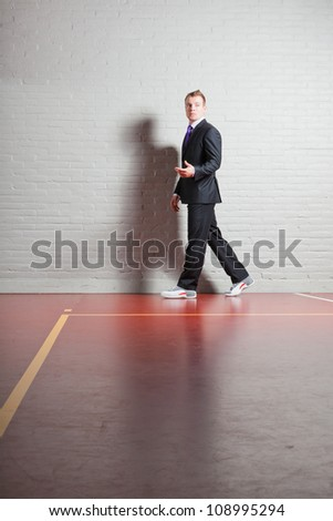 Good looking young man with blond short hair wearing dark suit and basketball shoes. Gym indoor. - stock photo