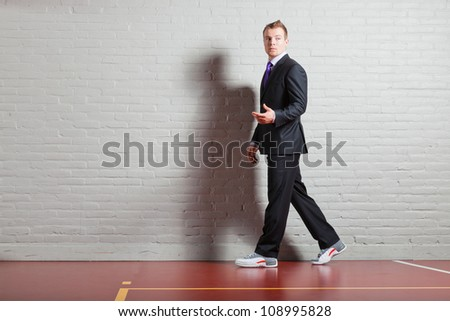 Good looking young man with blond short hair wearing dark suit and basketball shoes. Gym indoor.