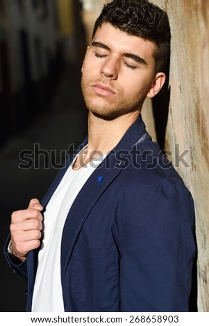 Good looking young man with blue eyes in the street. Model of fashion in urban background wearing white t-shir and blue jacket