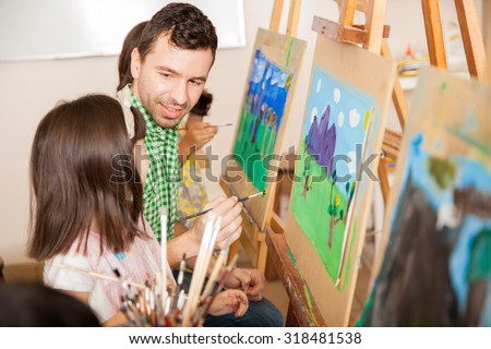 Good looking young teacher working on a painting with one of his students during art class - stock photo