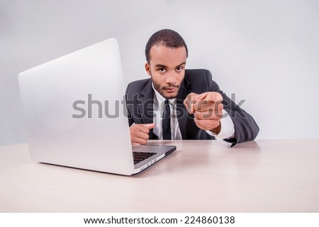 Good luck to you. Smiling African businessman sitting at a desk on a laptop while businessman sitting at the table and shows an index finger upwards over a laptop isolated on a gray background