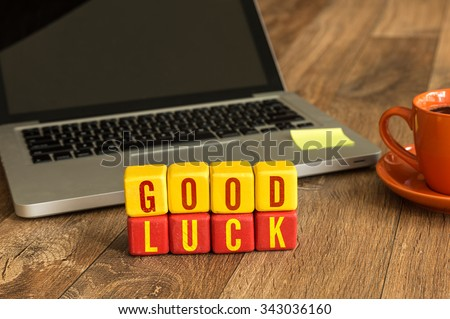 Good Luck written on a wooden cube in a office desk - stock photo