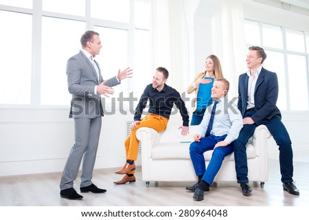 Good mood and creative work. Group of happy young business people laughing and listening their colleague while sitting on the couch. - stock photo