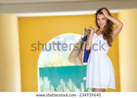 Good mood while shopping. Attractive young women is standing with shopping bags on the street and smiling. Girl is looking forward with smile - stock photo