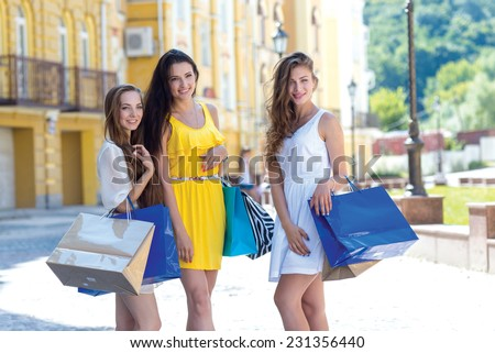 Good mood while shopping. Three young and pretty girls are holding the shopping bags and looking forward in a good mood - stock photo