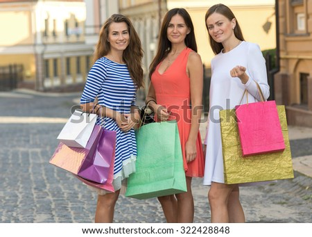 Good mood while shopping. Three young and pretty girls are holding the shopping bags and looking forward in a good mood. Happy shopping with smiles. Road to the mall