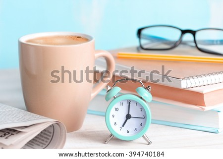 Good morning concept.Mug,alarm clock,newspaper,books,glasses on blue background.morning coffee day start.Education business place. - stock photo