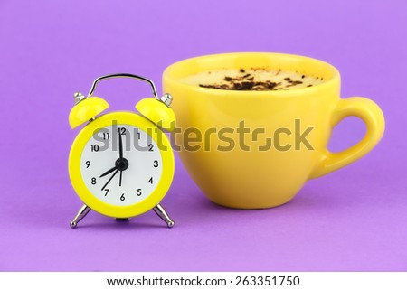Good Morning concept - yellow alarm clock with a yellow cup of cappuccino coffee for breakfast against purple background - stock photo
