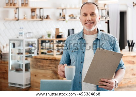 Good morning. Happy and confident senior man standing with folder and cup of coffee in hands in the cafe and smiling at a camera