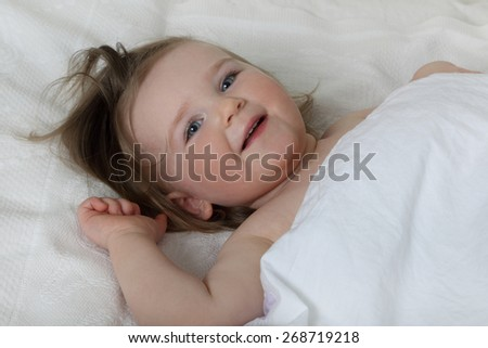 Good morning - Infant baby in bed under blanket woke up and smiles - stock photo