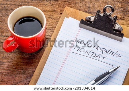 Good morning, Monday - handwriting on a small clipboard with a cup of coffee - stock photo