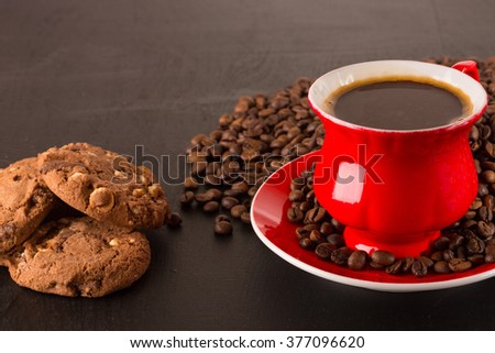 Good morning or Have a nice day message concept - bright red cup of frothy coffee with chocolate cookies, coffee beans