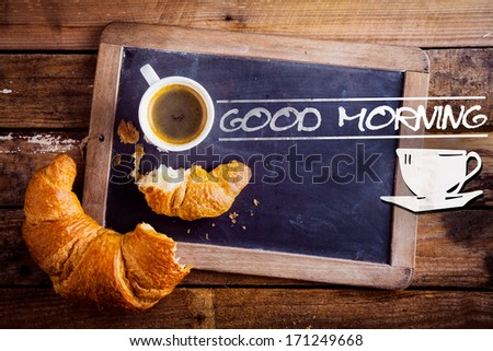 Good morning sign with a cup of fresh hot morning coffee and a broken croissant on an old school slate with a distressed wooden frame on a rustic table - stock photo