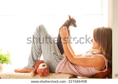 Good Morning! Teenage girl in pyjamas holding her small brown toy-terrier dog. Vibrant multicolored horizontal image. - stock photo
