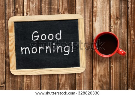 Good morning text on small blackboard and coffee cup - stock photo