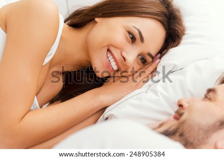Good morning! Top view of beautiful young loving couple lying in bed and looking at each other with smile  - stock photo