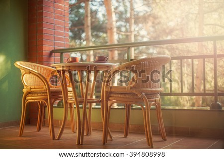 Good morning with a two cups of tea or coffee. Wicker furniture,coffee table and beautiful views of the pine forest. blurred background - stock photo
